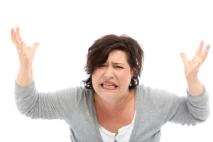 Distraught woman with her hands raised against white background.